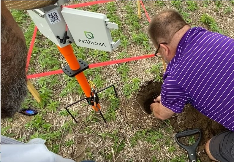 Tom McClain installs a soil probe into the field.